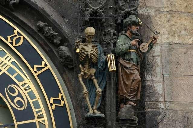 Фигурка смерти переворачивает песочные часы и дергает за веревку звонка, запуская представление апостолов