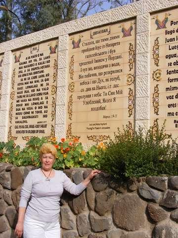 На каменном заборе, который тянется вдоль берега, написана цитата из Евангелия на многих языках мира.