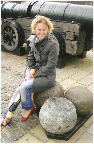 Девушка на ядре на фоне пушки в Замке в Эдинбурге